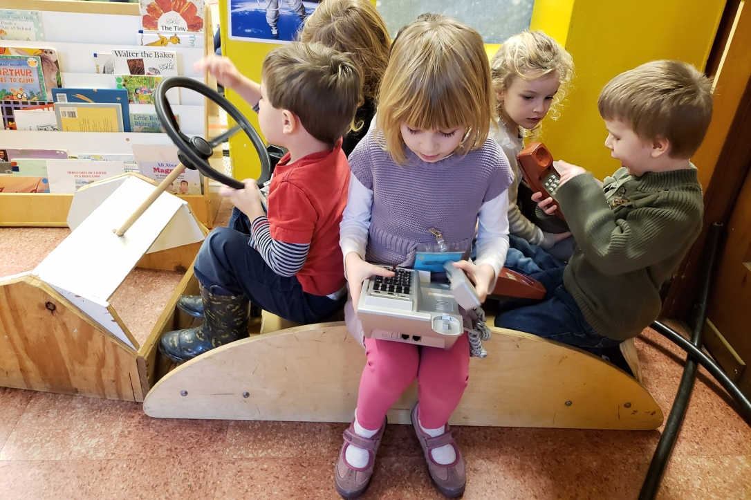 University-Ravenna Cooperative Preschool : Making important calls while driving a pretend car - dramatic play in the 3-5s Class